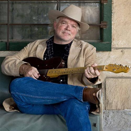 Image of Dallas Wayne sitting on a bench playing guitar