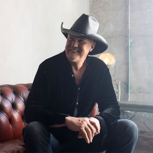 Image of Trace Adkins wearing a cowboy hat smiling and sitting on a red couch